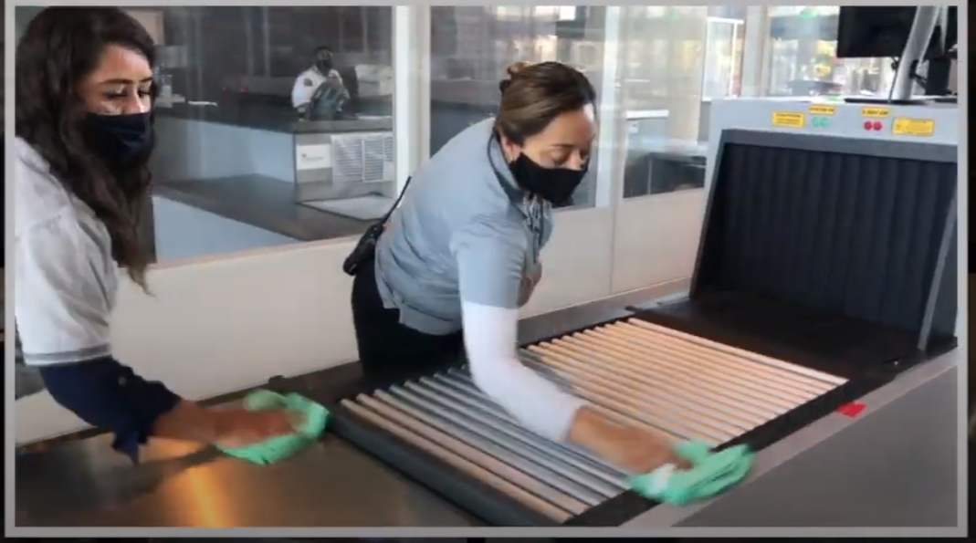 two femail staff wiping scanning equipment and wearing masks