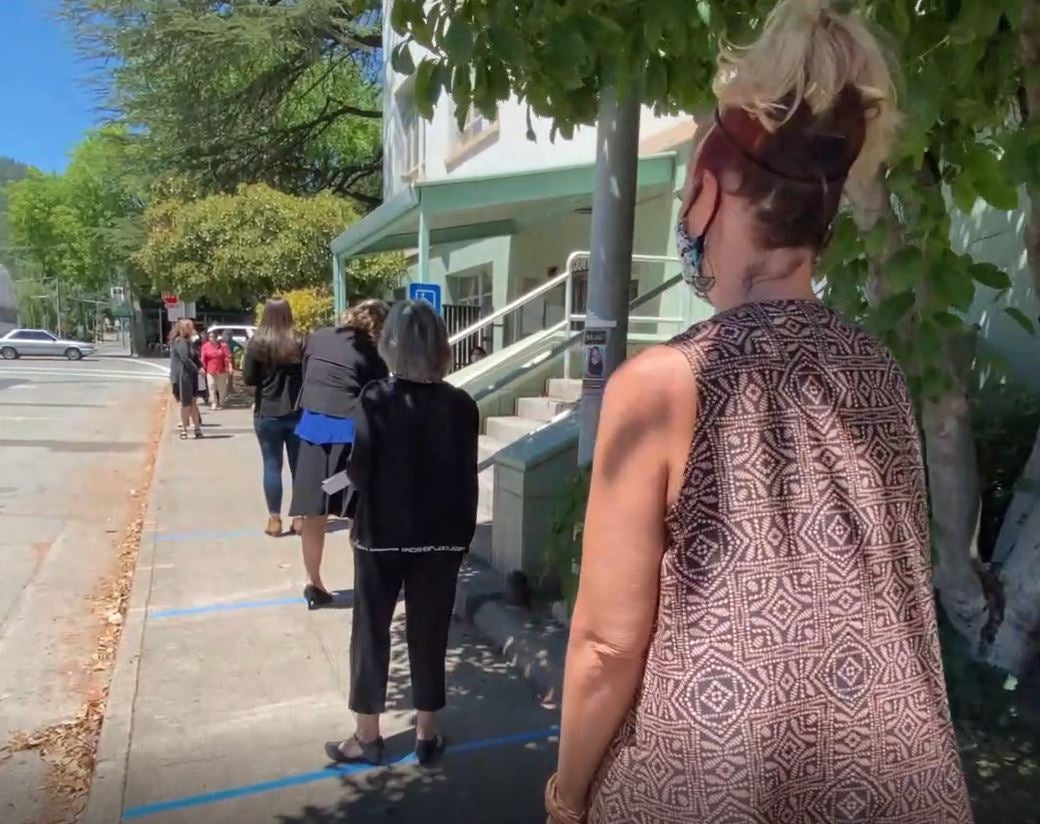 residents stand in line on sidewalk in the sun