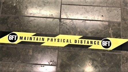 socially distance guidance on yellow and black floor tape