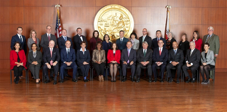 Judicial Council members seated in chairs and standing for official photo on wood stage