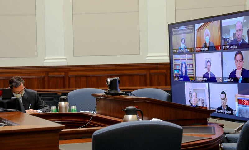 man seated in front of large screen tv in court