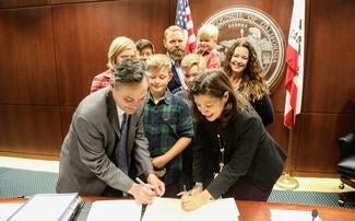"Chief Justice Tani Cantil-Sakauye and Administrative Director Martin Hoshino sign the resolution proclaiming November ""Court Adoption and Permanency Month."""